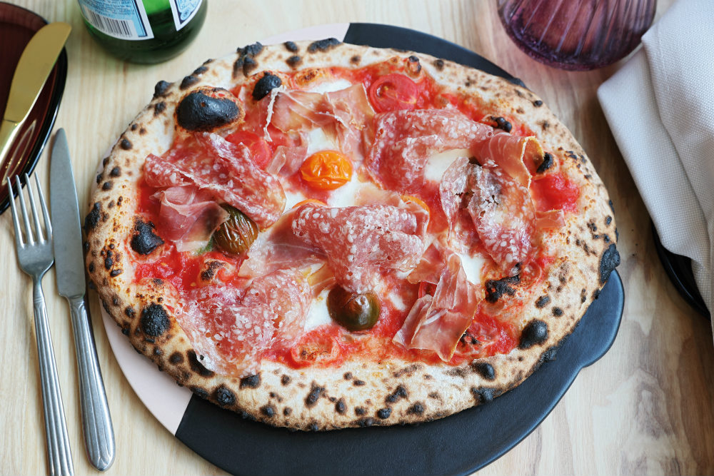 Saint Restaurant Pizza with cured meats, fresh tomato and taleggio cheese
